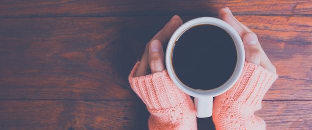 Mano de la mujer en el suéter caliente que sostiene una taza de café en un fondo de madera de la tabla