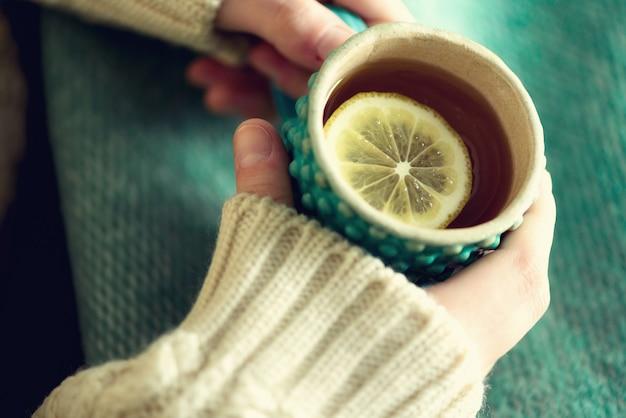 La mano de la mujer en el suéter de lana que sostiene la taza de té con el limón en un día frío. copia espacio concepto de vacaciones de invierno y navidad.