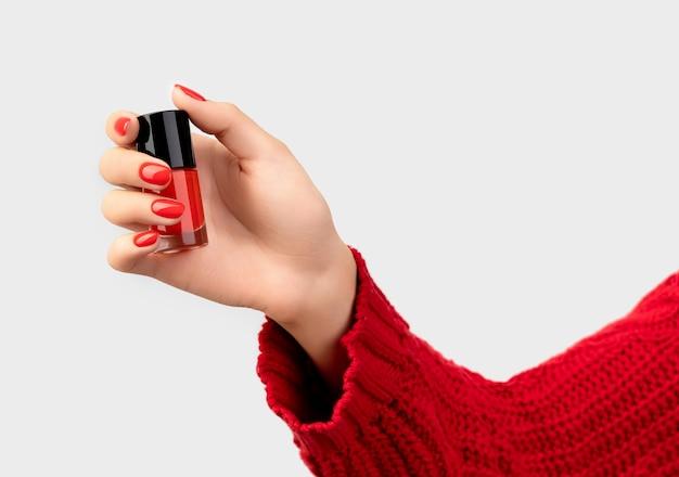 Mano de mujer en suéter con manicura roja sosteniendo una botella de esmalte de uñas