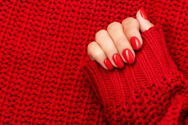 Mano de mujer en suéter con manicura rojo sobre gris