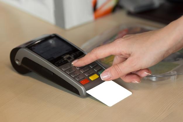 Mano de mujer con tarjeta de crédito pase a través de terminal para la venta en restaurante.
