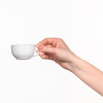Mano de mujer con taza blanca perfecta sobre fondo blanco.