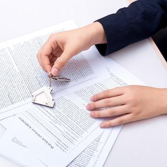 Mano de mujer y tecla de inicio. contrato firmado y claves del inmueble con documentos.