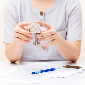 Mano de mujer y tecla de inicio. contrato firmado y claves de la propiedad con documentos.
