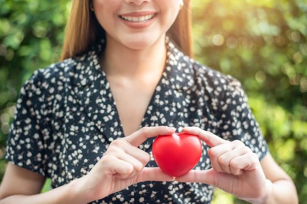 Mano de mujer tiene corazón rojo
