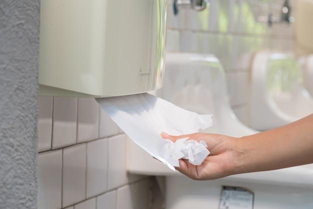 Mano de mujer tirando de un pañuelo blanco de pañuelos de papel en el baño