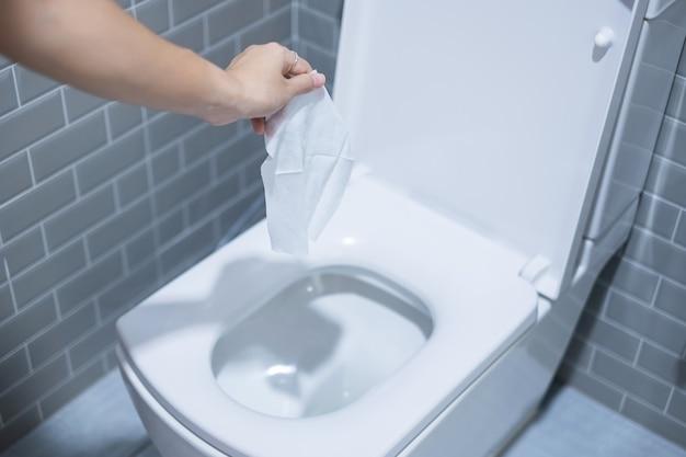 Mano de mujer tirar toallas de papel en la taza del inodoro. concepto de limpieza, estilo de vida e higiene personal.