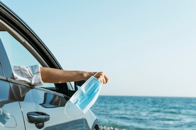 Mano de mujer de tiro medio fuera de la ventana del coche y sosteniendo la mascarilla cerca del mar