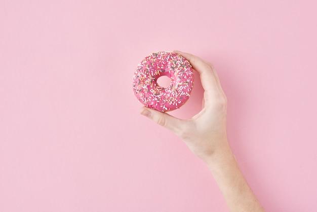 La mano de la mujer toma color donut en rosa. concepto de comida de estilo minimalismo de creatividad, vista superior