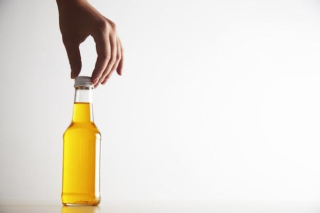Mano de mujer toma cuidadosamente la botella con bebida amarilla en el interior de cuello largo