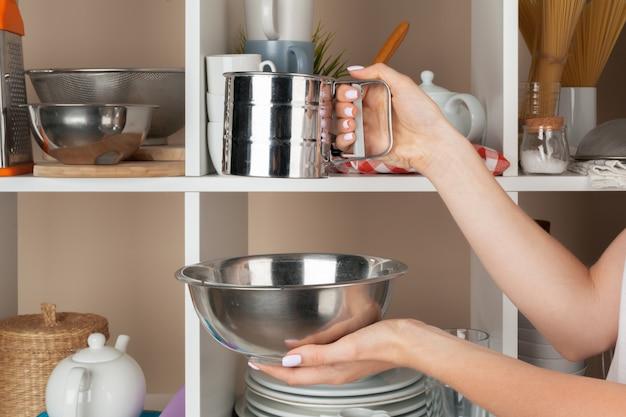 Mano de mujer tomando piezas de vajilla del estante en la cocina