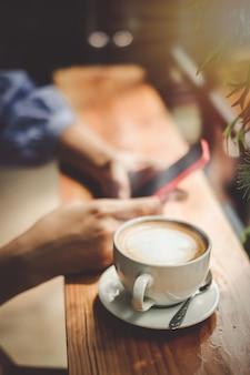Mano de mujer tomando y usando el teléfono móvil y tomando café en la cafetería