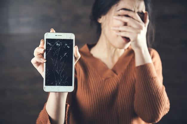 Mano de mujer triste roto teléfono inteligente