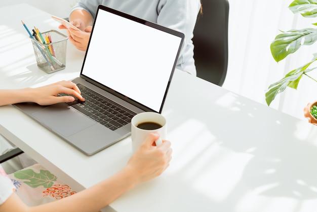 Mano de mujer usando la computadora portátil en la mesa en la casa, simulacro de pantalla en blanco.