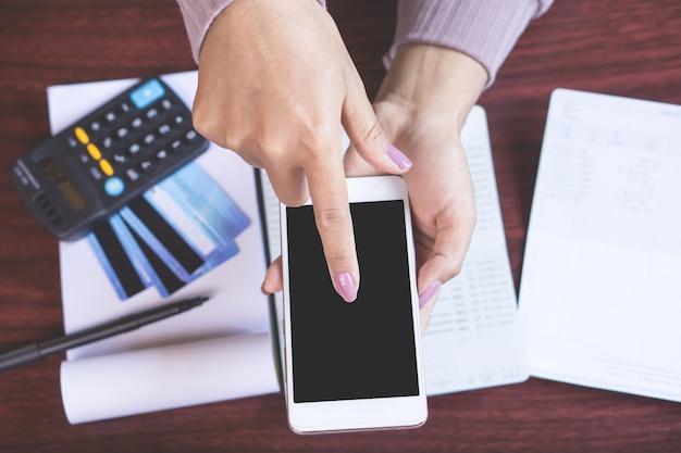 Mano de mujer usig teléfono inteligente calcular gastos
