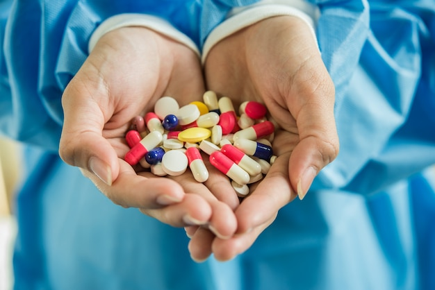 Mano de mujer vierte las pastillas de la medicina fuera de la botella