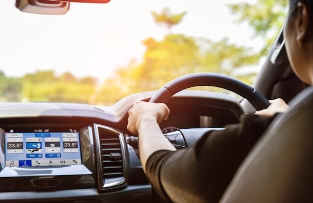 Mano de la mujer en el volante de cuero del coche mientras que conduce por la mañana. concepto de transporte.