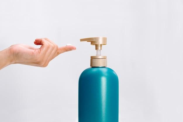 La mano de las mujeres aplica la botella del acondicionador del champú del pelo en el fondo blanco.