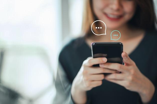 Mano de las mujeres escribiendo en teléfonos inteligentes móviles, chat en vivo en la aplicación comunicación web digital y concepto de red social. trabajar desde casa.