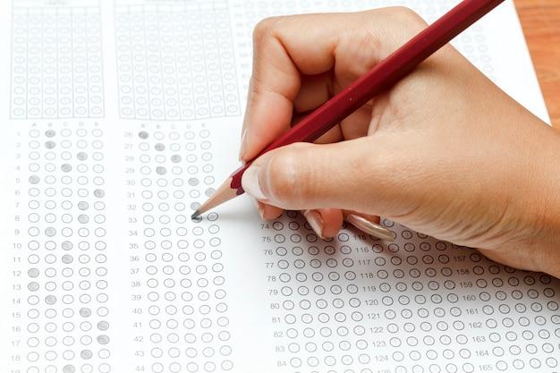 Mano de mujeres con lápiz en forma de prueba estandarizada con respuestas burbujeadas y un lápiz, enfoque o