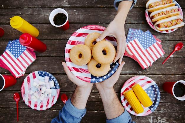 Mano de las mujeres tomando donut
