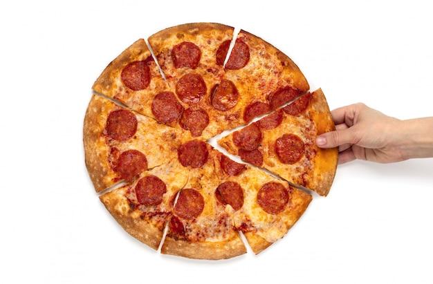 La mano de las mujeres de la vista superior toma una rebanada de pizza de salchichones en el fondo blanco aislado.