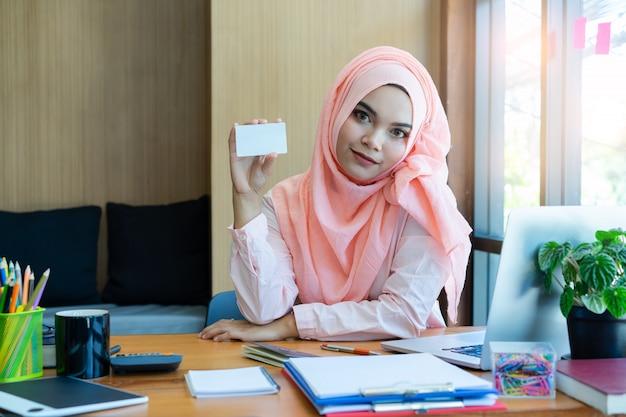 Mano musulmana hermosa de la mujer de negocios que sostiene la tarjeta de crédito en blanco en oficina moderna. tarjeta de crédito en blanco
