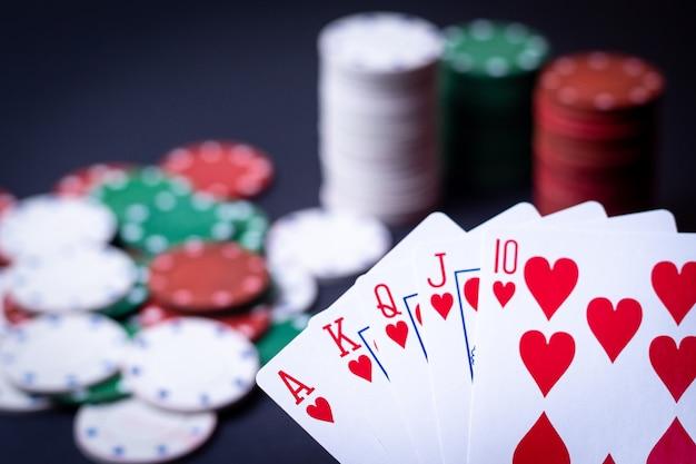 Mano de naipes de escalera real con fichas de póker