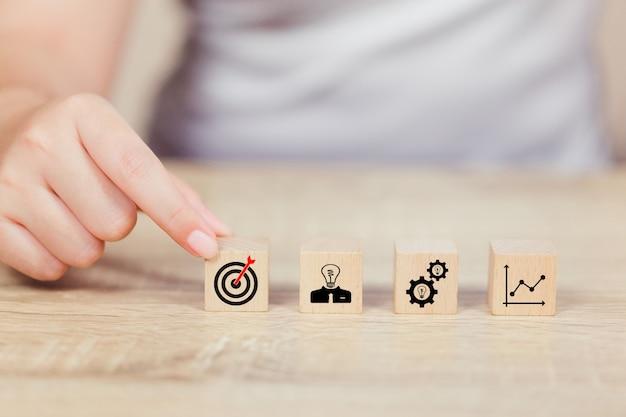 Mano de negocios arreglando el bloque de madera con la estrategia empresarial de icono