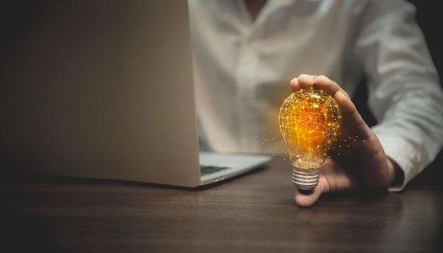 Mano de negocios que sostiene la bombilla, la creatividad y la innovación son claves para el éxito