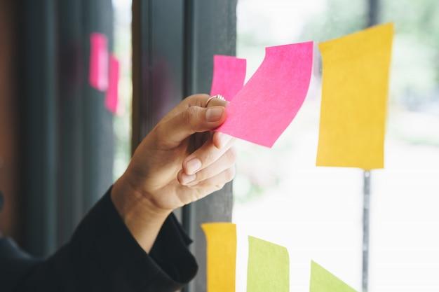 Mano de negocios recogiendo notas adhesivas en la pared de cristal.
