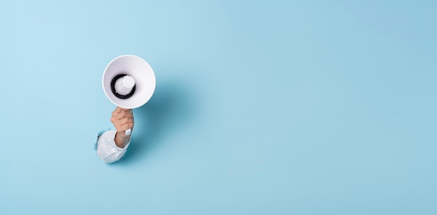 Mano de negocios sostiene un megáfono de un agujero en la pared sobre fondo azul. contratación, publicidad, publicidad y concepto de banner.