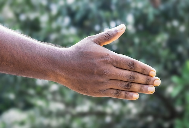 Una mano negra que se extiende hacia para ayudar o dar un apretón de manos.