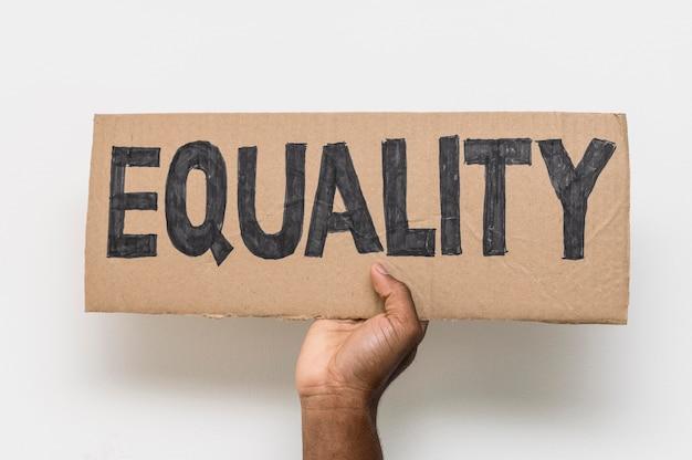 Mano negra sosteniendo la igualdad en cartón