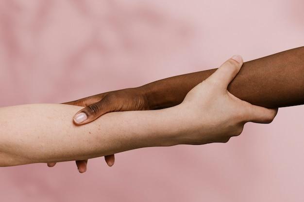 Mano negra sosteniendo la mano blanca