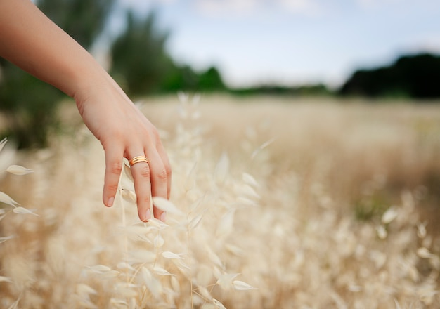 Mano de niña con anillo casado acariciando hojas secas.