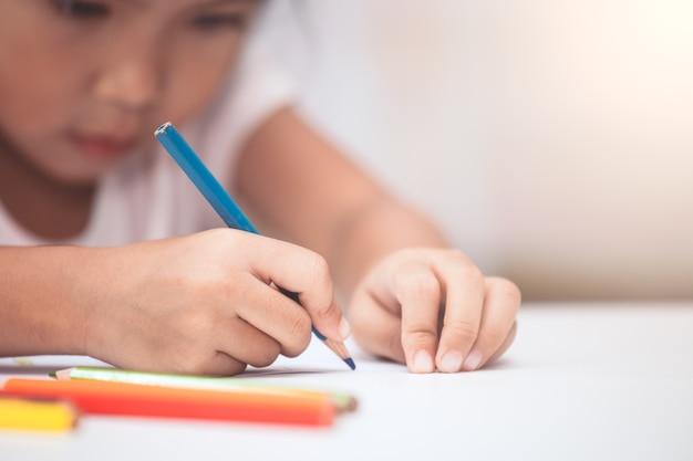 Mano de niña asiática dibujar y pintar con crayón en tono de color vintage