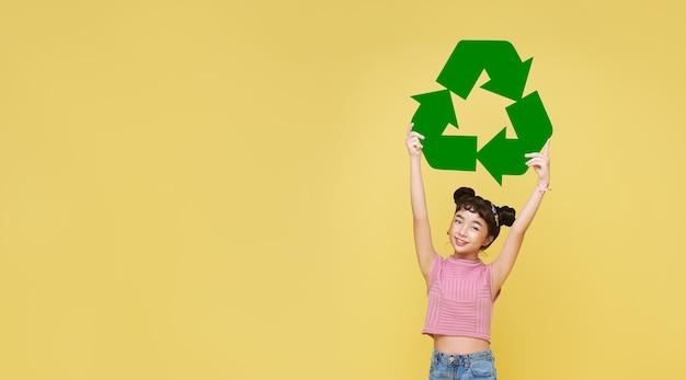 Mano de niña asiática feliz sosteniendo el símbolo de reciclaje sobre fondo amarillo. concepto ecológico y de reutilización.