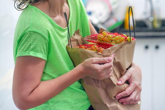 Mano de niña con bolsas de comida en casa.
