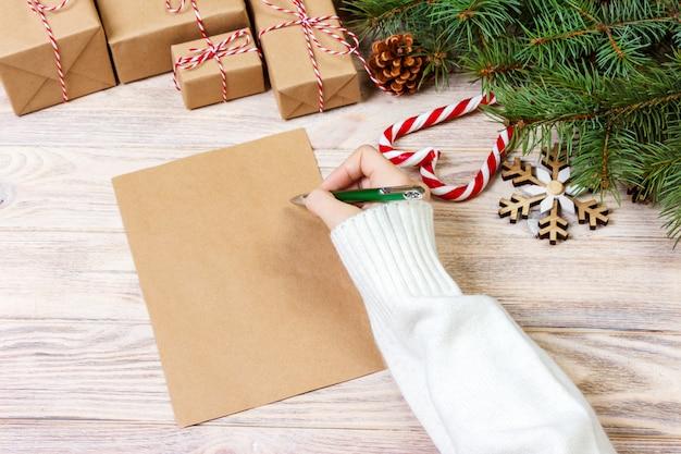 Mano de niña escribir carta de navidad en papel artesanal con decoraciones en madera