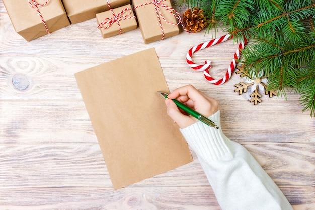Mano de niña escribir carta de navidad en papel artesanal con decoraciones