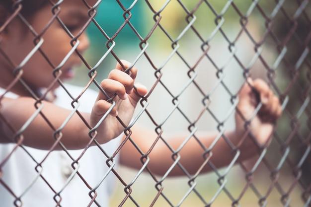 Mano de niña de niño con malla de acero en tono de color vintage