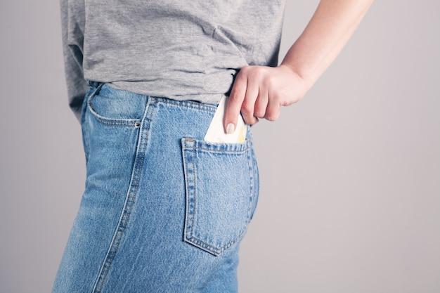 Mano de niña poniendo dinero en el bolsillo de los pantalones vaqueros