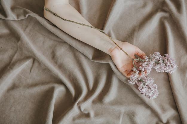 Mano de una niña con una rama lila en una cama en una hoja arrugada