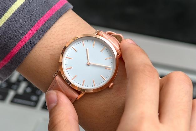 La mano de la niña con reloj de pulsera frente a una computadora portátil