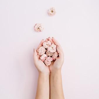 Mano de niña sosteniendo capullos de rosas secas rosadas en rosa