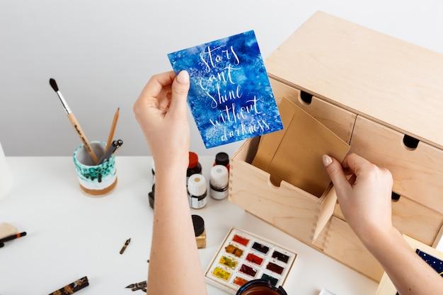 La mano de la niña sosteniendo una postal con palabras las estrellas no pueden brillar sin la oscuridad.