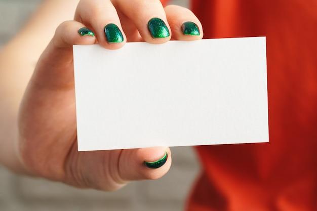 Mano de niña sosteniendo tarjetas en blanco blanco