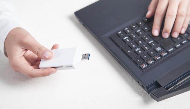 Mano de niña sosteniendo una unidad flash usb con una computadora portátil en el escritorio.