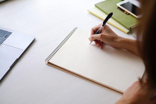 La mano de las niñas escribe con un bolígrafo en una hoja de papel en blanco